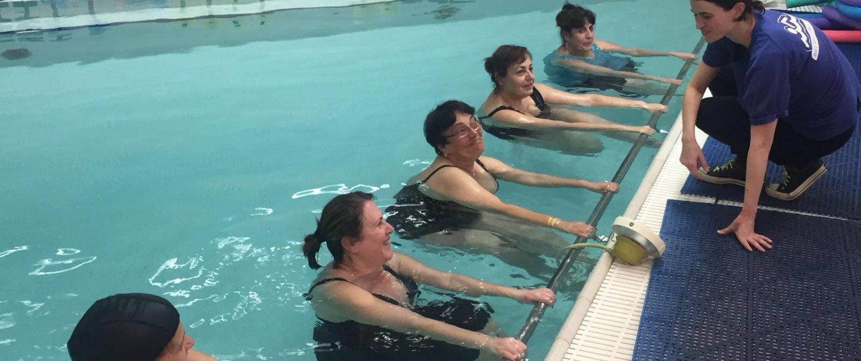 מדריכה בבריכה יחד עם המתעמלות שלה בחוג התעמלות במים