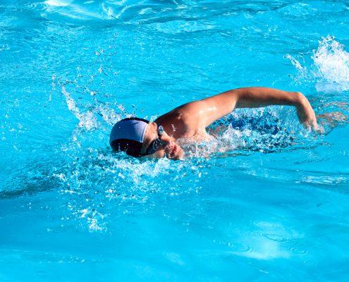 לימוד שחייה למבוגרים - בחור שוחה בבריכה בשיעור לימוד שחיה למבוגרים
